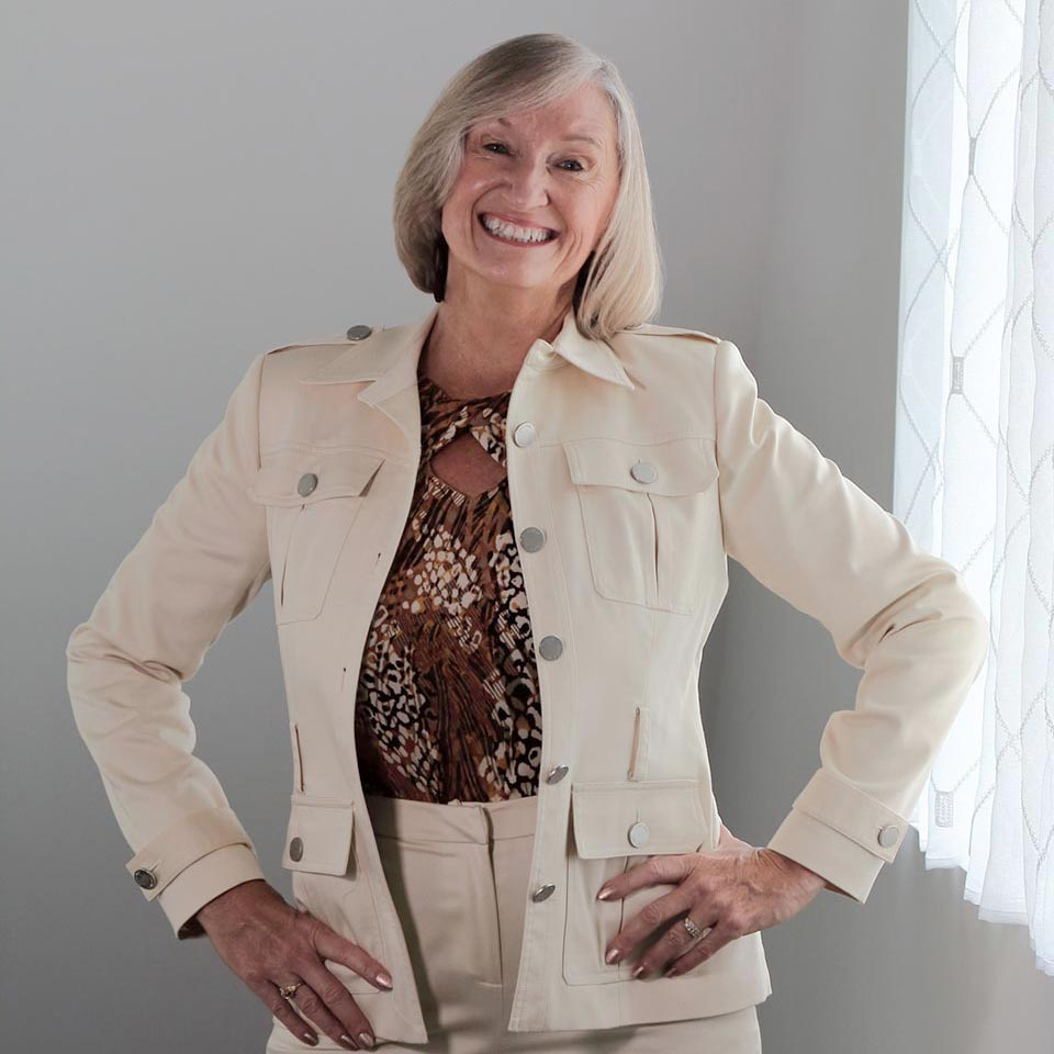 Michele smiling and posing in a Calvin Klein pant suit
